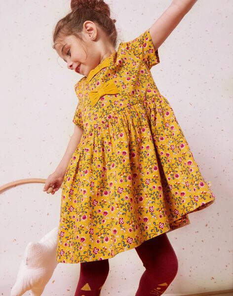 petite fille avec une robe jaune à motifs qui joue